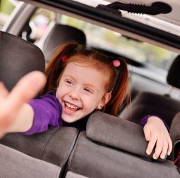 baby cute red-haired girl smiling in car salon
